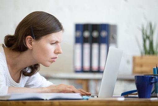 En kvinne lener seg fremover for å klare å se skjermen på en laptop.