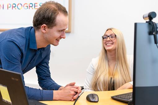 Bilde av to en mann og en kvinne som smiler på jobb foran en pc. Fotografi