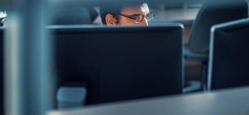 Bilde av en mann som kikker på flere dataskjermer i et kontorlandskap. Fotografi