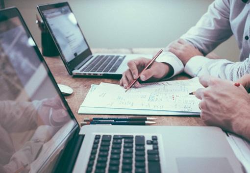 Bilde av to menneskehender som viser noe på et ark mellom to laptoper. Fotografi