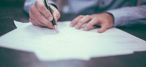 En hånd signerer noen dokumenter med en dyr penn. Fotografi