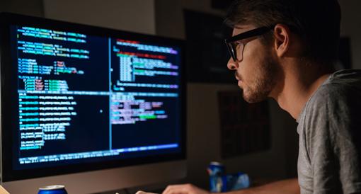 Bilde av en mann ser på kode på en dataskjerm. Fotografi