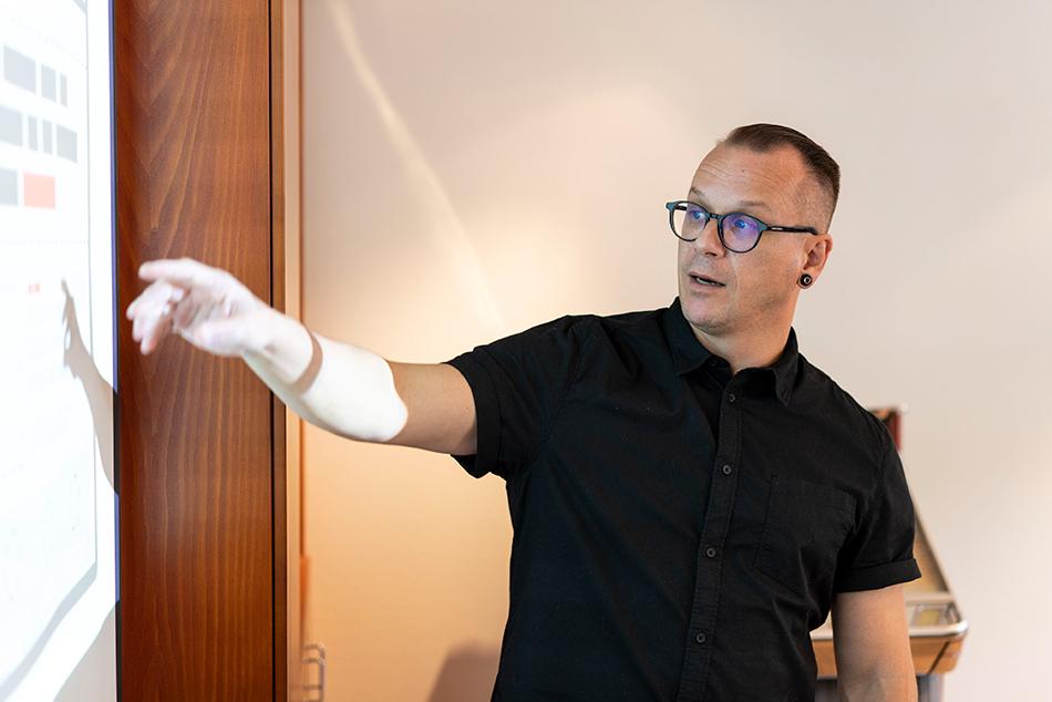 Robert Macli fra ItumX peker på en stor skjerm. Han holder en presentasjon.