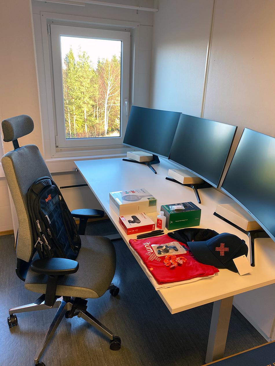Bilde av et kontor, med en kontorstol med ItumX-sekk, og kontorpult med mange goodiebag-artikler på. Foto