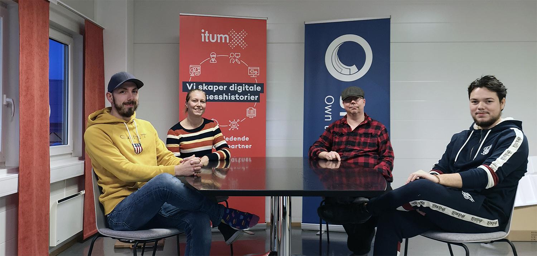 Fire mennesker sitter rundt et møtebord og smiler til kamera. Foto