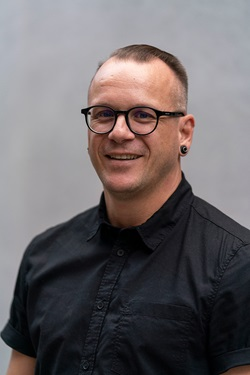 Portrettbilde av en smilende Robert Macli. Fotografi